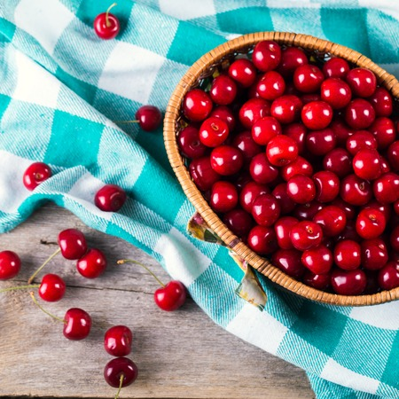 Closeup of basket with fresh cherries on wooden backround Stockfoto