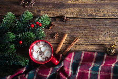 espresso cup: red cup with cocoa and marshmallows on wooden background. Christmas presents and candles