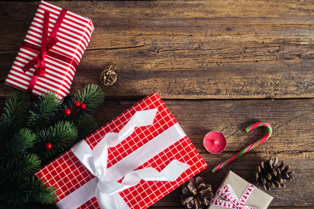 present box: Christmas presents on a wooden background with candy cane, fir branches, candle, cones.