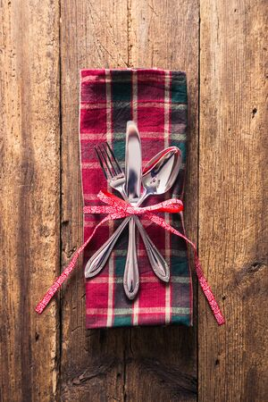 grunge cutlery: Cutlery on checkered napkin with ribbon branch on wooden background. Christmas background.