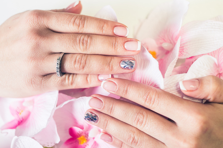 salon background: Beautiful gel lacquer. French manicure with silver diamonds. Womens hands. Stock Photo