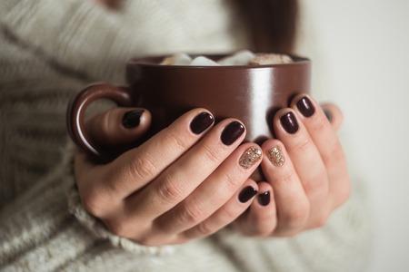 여자의 손에 코코아와 마시 멜로 브라운 컵.