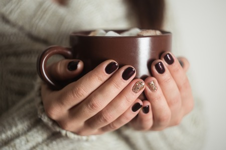 Brown cup with cocoa and marshmallow in the hands of the girl.