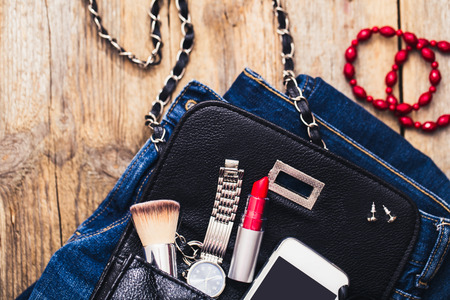 Fashion accessories for a young girl, watch, bracelet, handbag, red lipstick, telephone, brush on a wooden background. Stockfoto