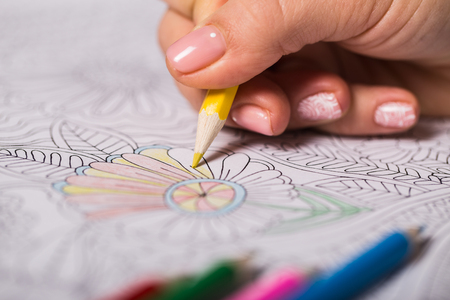 Girl paints a coloring book for adults