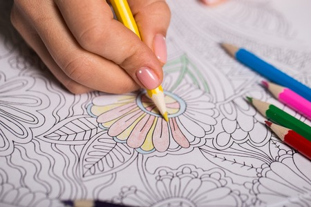 adults: Girl paints a coloring book for adults