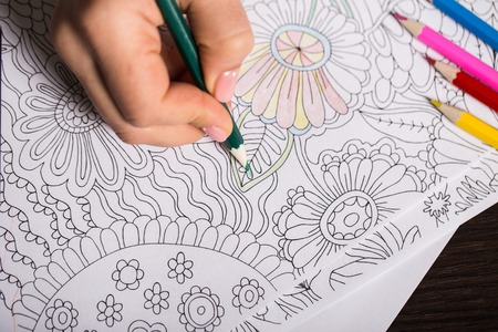 pensil: Girl paints a coloring book for adults