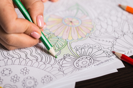 pensil: Girl paints a coloring book for adults with crayons