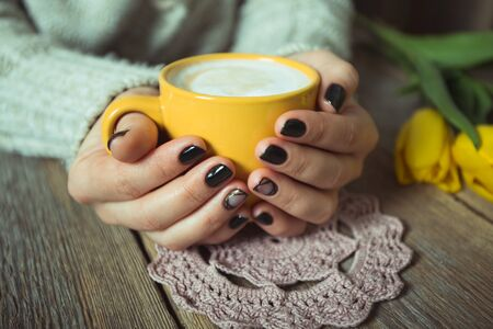 winter girl: Yellow cup in the hands of women. Gel nail manicures. Phone and the magazine on the table Stock Photo