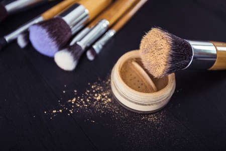black makeup: make up brushes with powder and rouge on a black wooden background