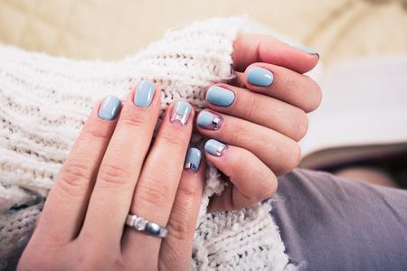 acrylic nails: beautiful manicure. Gel polish coating in blue, embossing. Stock Photo