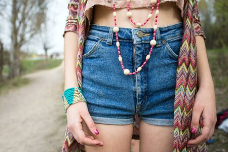 denim shorts: young girl in denim shorts, jewelry accessories.