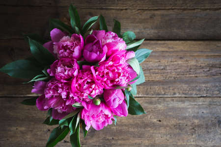 peonies: fresh pink peonies on a wooden background