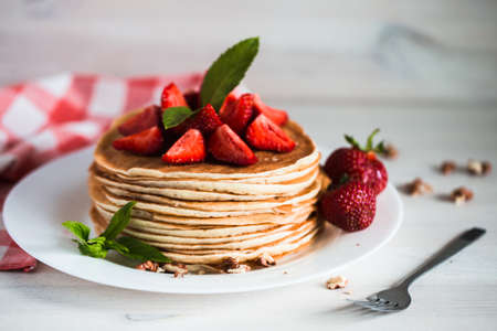batters: Delicious pancakes with strawberry on wooden background