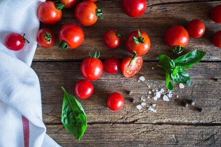 Fresh grape tomatoes with basil and coarse salt for use as cooking ingredients with a halved tomato in the foreground with copyspace Stock Photo