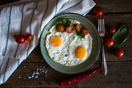 scrambled: Scrambled eggs with tomatoes on wooden background