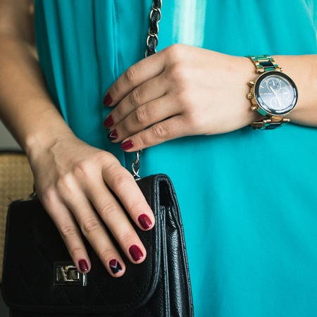 clutch bag: Female nails with red nail polish and a beautiful black handbag