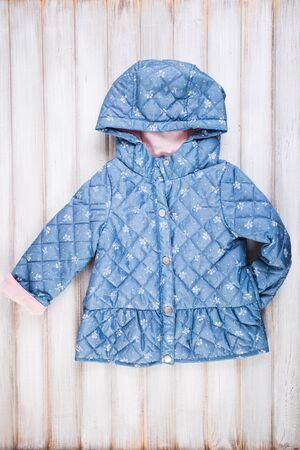 warm jacket: Baby blue warm jacket on wooden background