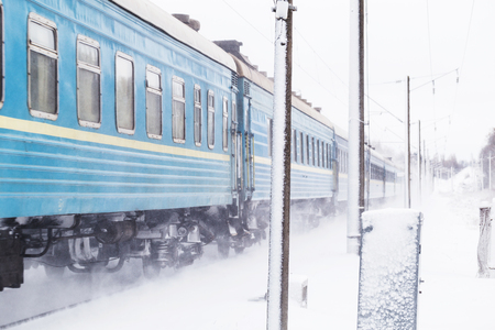 rapidly: Passenger train rapidly moving along the snow track