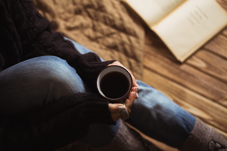 Woman with beautiful manicure holding a gray cup of tea and reading a book