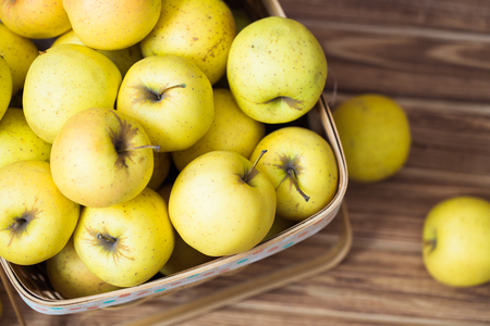 Golden apples in a basket on a wooden background Banco de Imagens