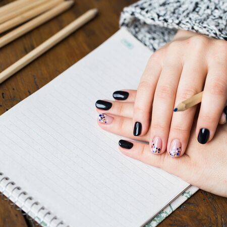 pointed arm: A woman with a beautiful manicure draws in a notebook