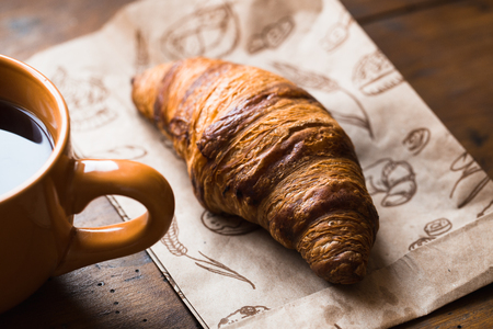 Coffee croissant on old wooden table background Stock Photo