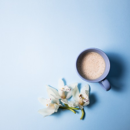 Cup of coffee and orchid flower on a blue background