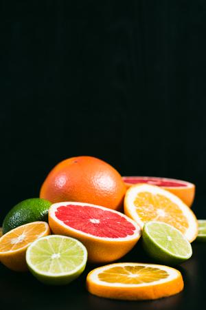 Citrus frais d'agrumes. Citrons, limes, pamplemousses et orange sur fond noir Banque d'images - 75939832