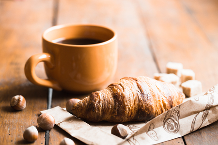 Coffee croissant on old wooden table background Stockfoto