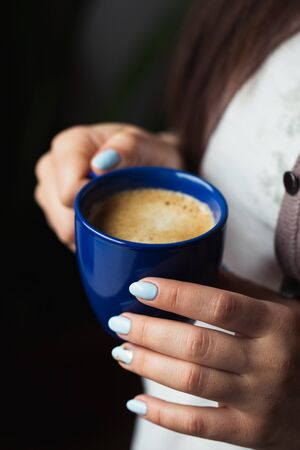Girl with blue manicure holds a blue cup of coffee Stock Photo