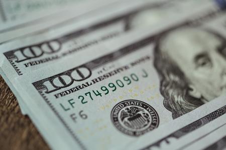 アメリカのドル紙幣は古い木製の背景に広がる