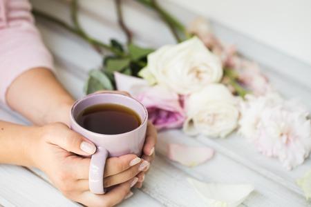 木製の背景にお茶のカップを保持している女性。朝、飲み物、休憩