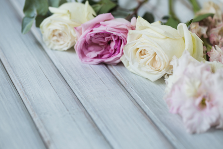 White and pink roses flowers on white painted wooden background. Selective focus. Place for text. Stock Photo