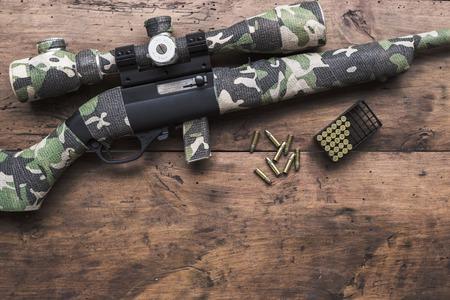 Kleine kaliber 22 lange geweer met een optisch zicht en cartridges in camouflage tape