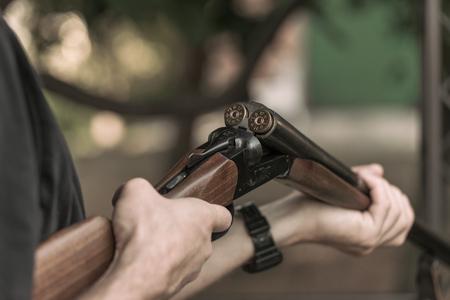 Man charging double-barreled hunting rifle closeup