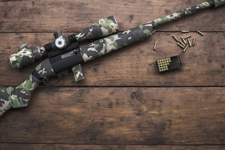 Small caliber 22 long rifle with an optical sight and cartridges in camouflage tape Stock Photo