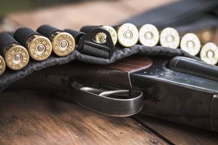 Shotgun with cartridges on a wooden background Stock Photo
