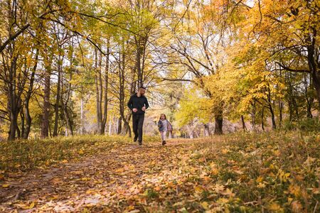 daughter runs away from her father in the autumn forest