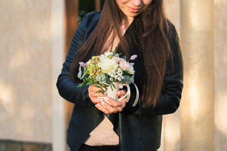 The girl is holding a beautiful bouquet of flowers in her hands