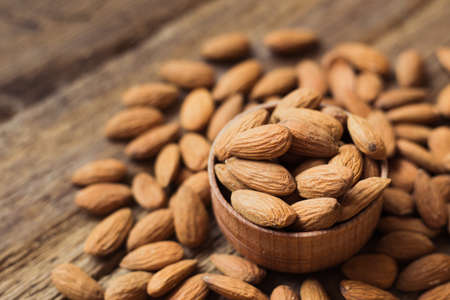 Almonds in brown bowl on wooden background Stock Photo