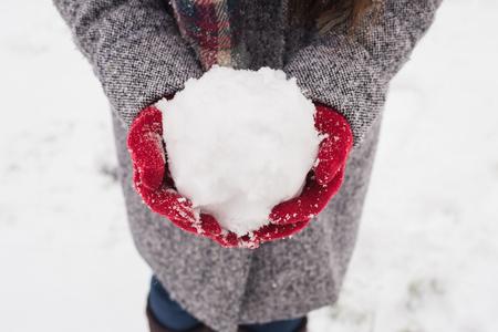 メリークリスマスの挨拶で雪を持つ赤い覆われた手袋を着た女の子