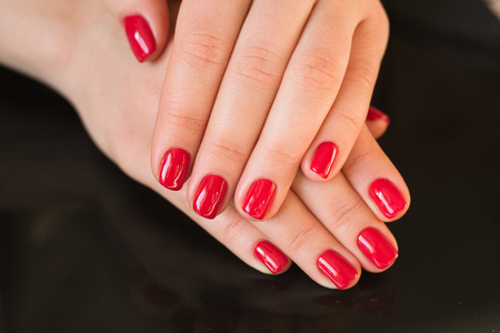 red manicure with nail on a black background
