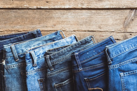 Jeans stacked on a wooden background Foto de archivo