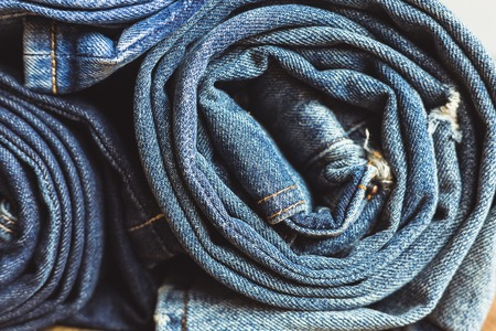 Jeans stacked on a wooden background Stock Photo