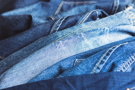 Jeans stacked on a wooden background Banque d'images - 98693464