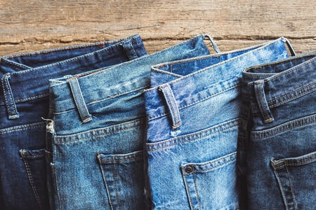 Jeans stacked on a wooden background Imagens