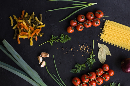 Fresh ingredients for cooking pasta, tomatoes, onions, garlic, herbs, mushrooms and spices on a black table background with copy space 免版税图像