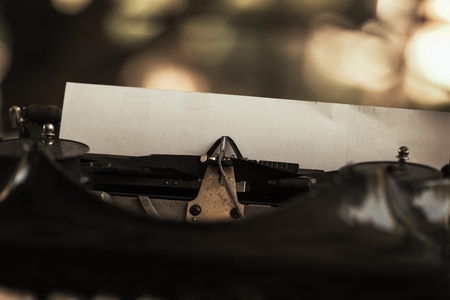 Old black typewriter with paper worth on the table Stock Photo