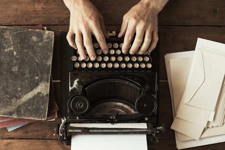 Young mans hands typing on an antique vintage typewriter